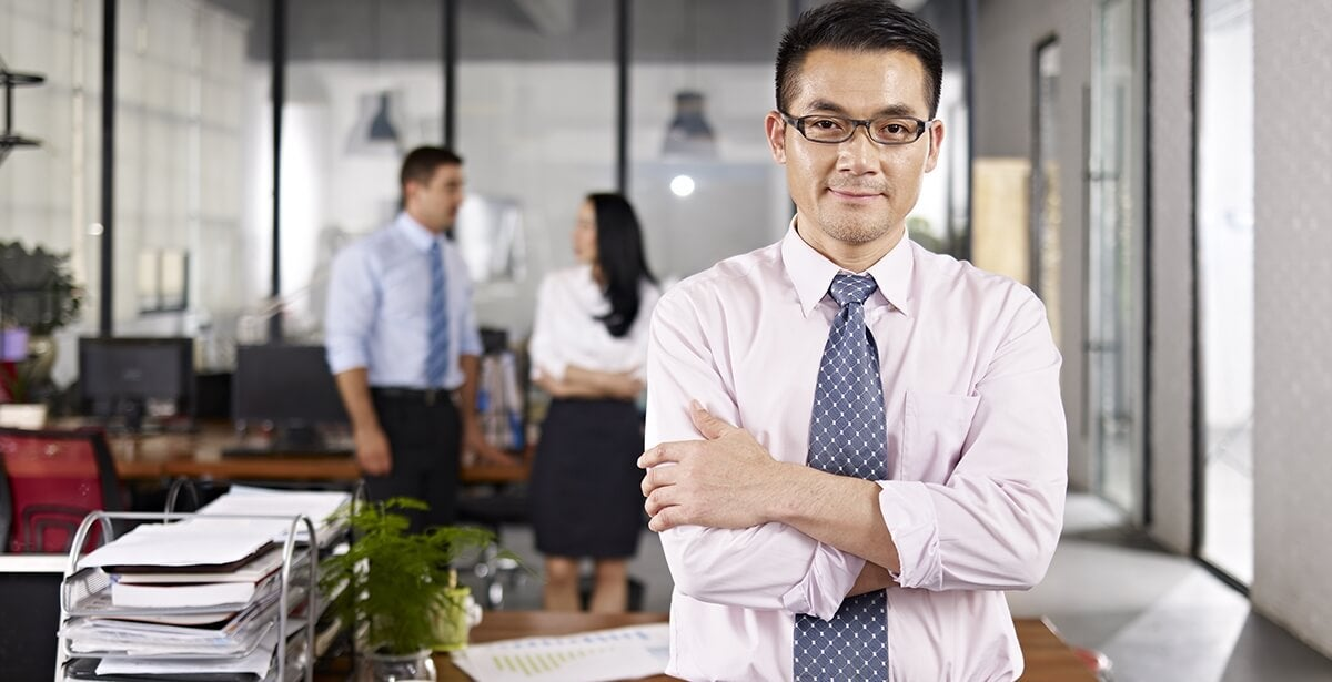A confident online MBA graduate, and advocate for change, leans against his desk.