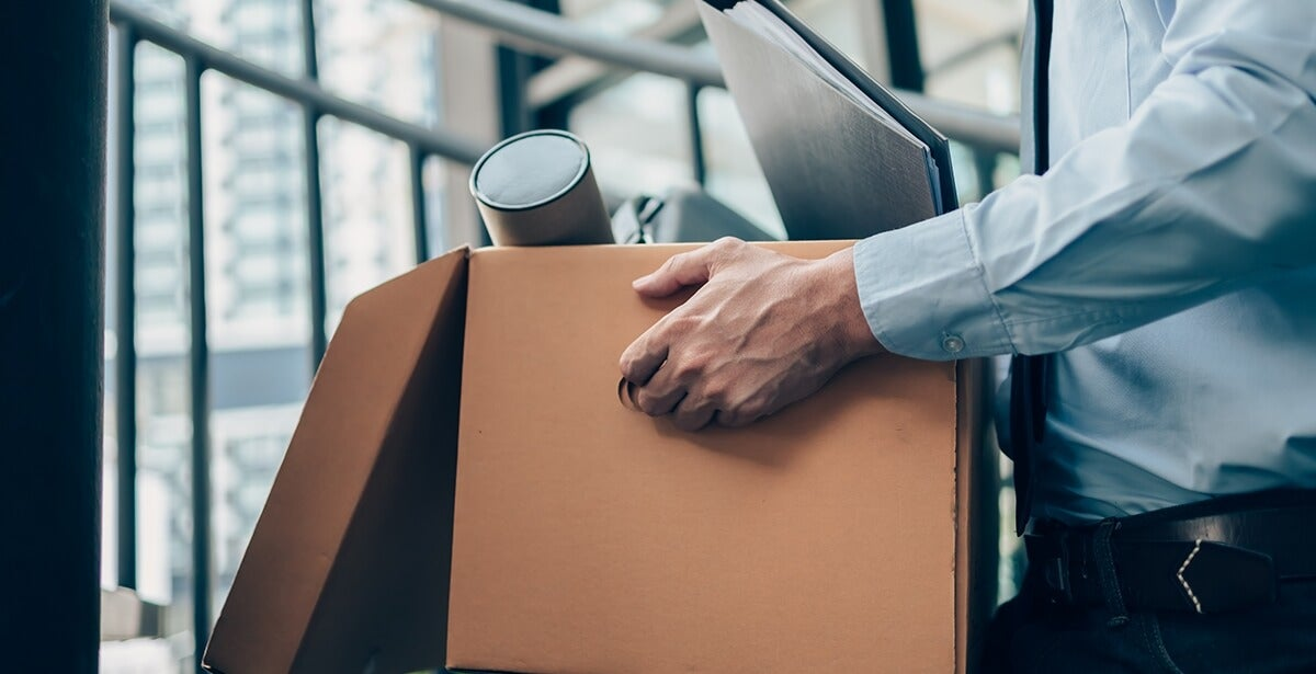 Man leaves office with box in hands after quitting job