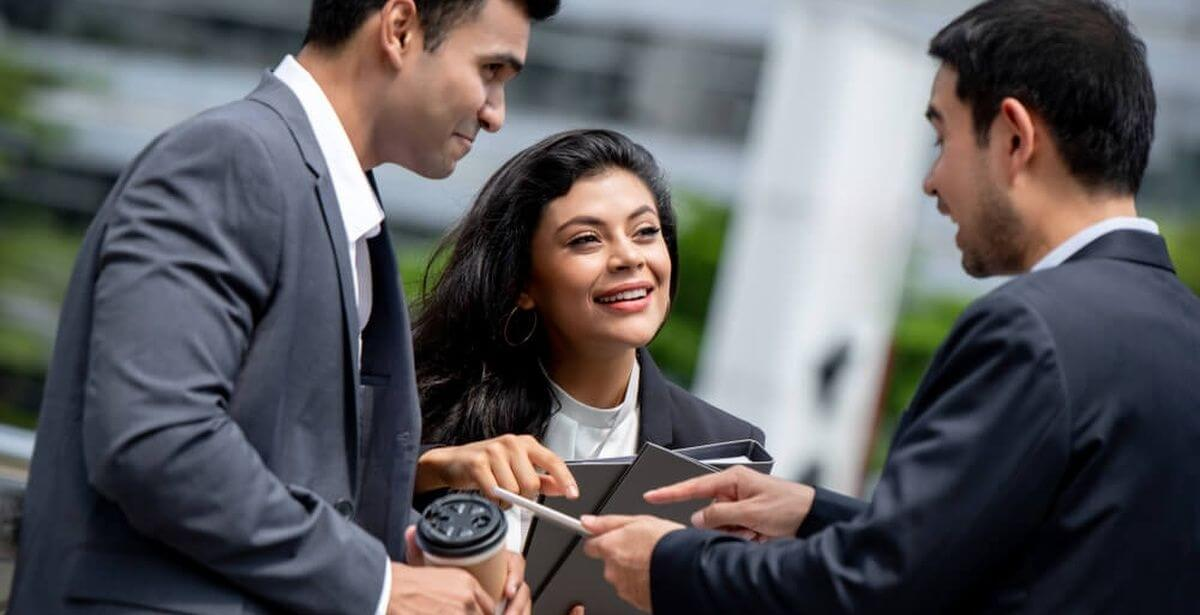 A group of three mixed-gender business professionals in suits having an animated conversation outdoors
