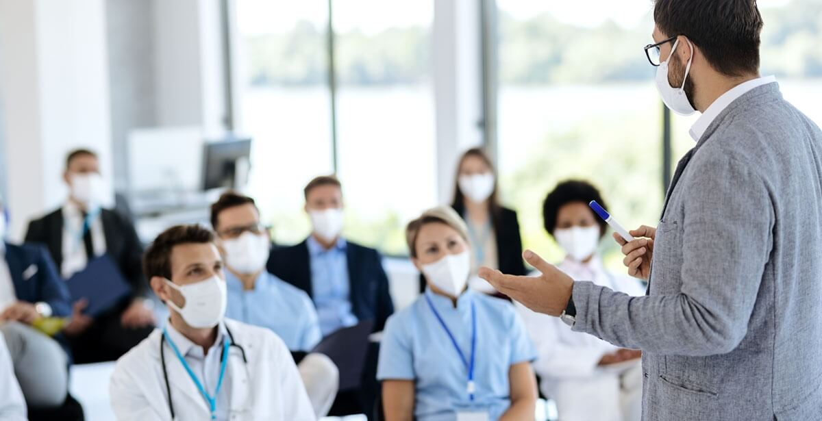 Suffolk MBA Online program graduate addresses team of healthcare professionals wearing masks.
