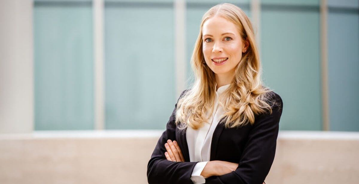Confident looking female business professional with arms crossed standing in front of an office building